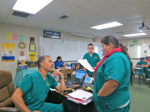 Teacher Simon Moore speaks with a student at Coachella Valley High School's Health Careers Academy.